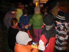 Rozdávání balíčků dětem urozsvíceného stromu.